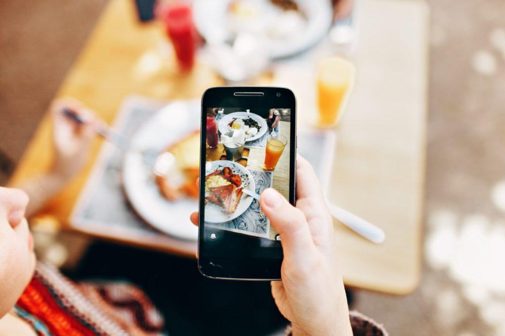 mujer fotografiando comida con un smartphone