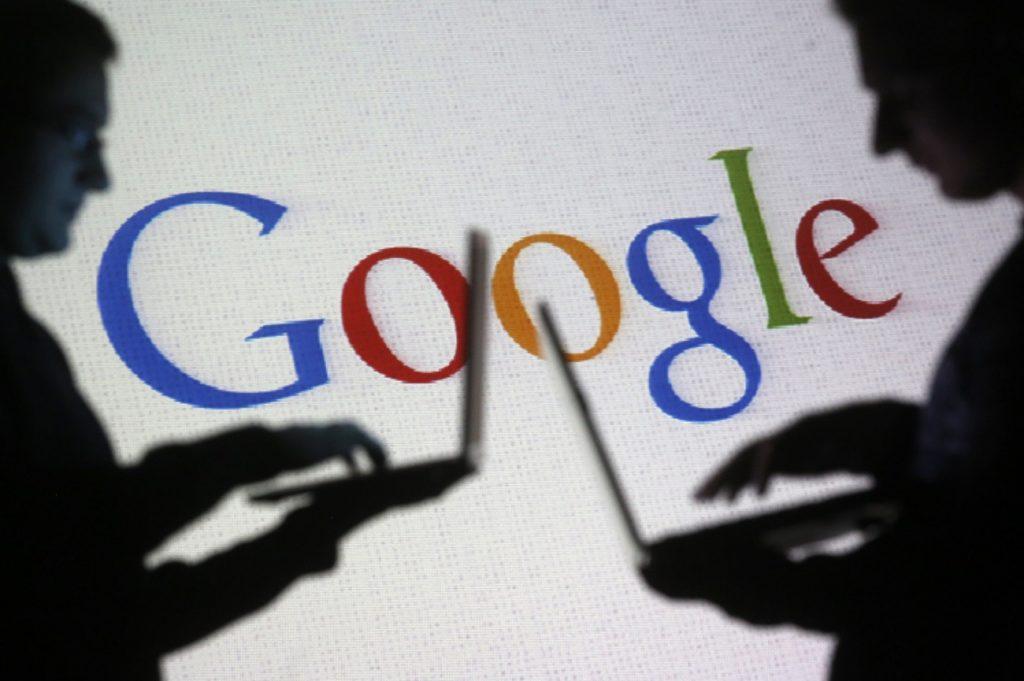 personas navegando frente a una pantalla con logotipo de google